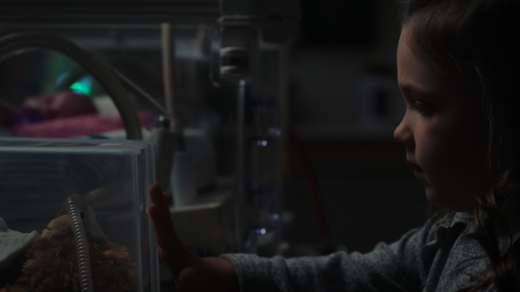 little girl looks into incubator where her preemie brother lies