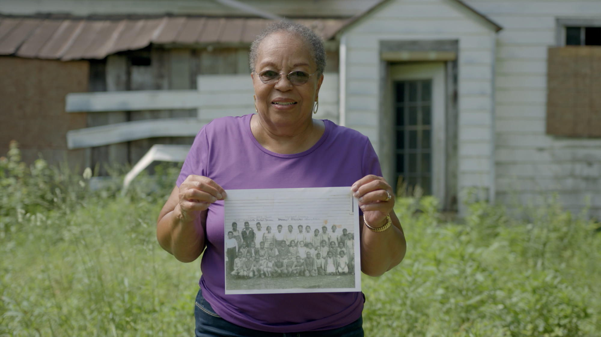 former rosenwald student now elderly woman holds up old school photo