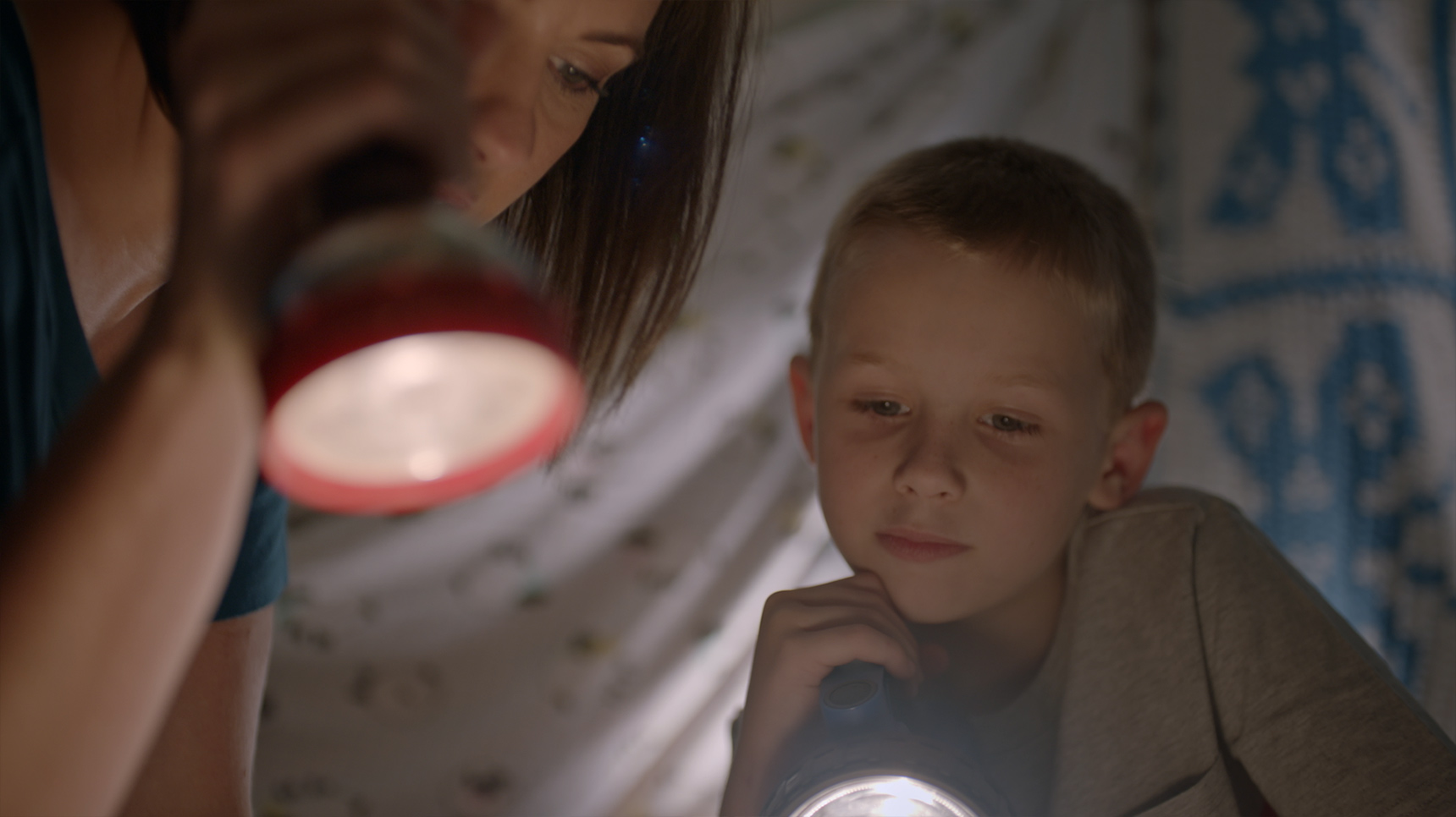 mother and son read book in tent with flashlights in his bedroom